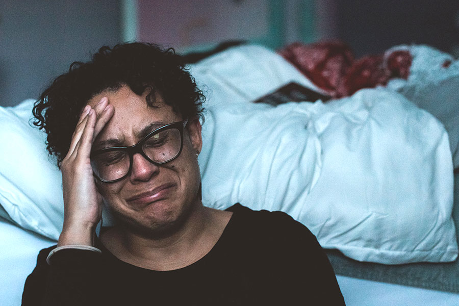 caregiver crying beside bed
