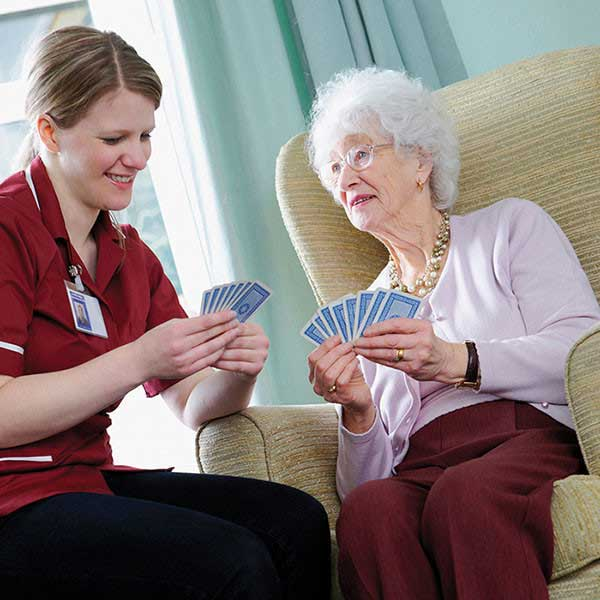 caregiver and client playing cards together