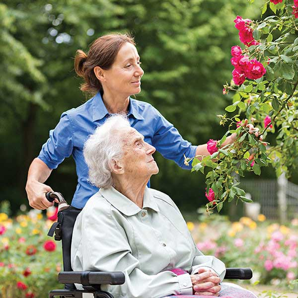 caregiver assisting an elderly in wheelchair