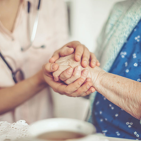 caregiver holding the hand of an elderly woman